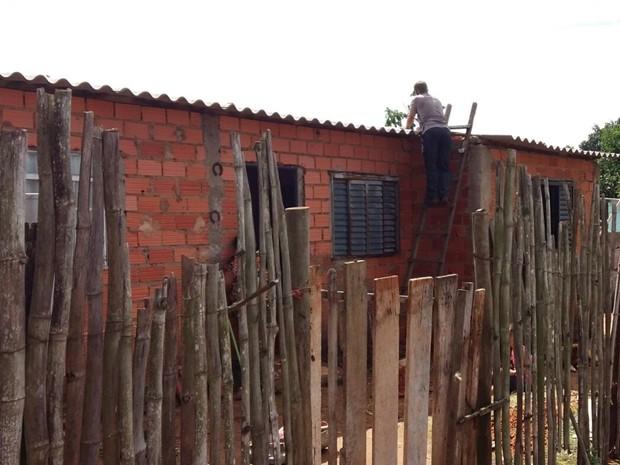 Morador arruma telha afetada por chuva de domingo (Foto: Adolfo Lima/ TV TEM)