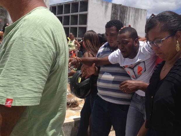 Marido se despera em sepultamento da mulher em Camaçari (Foto: Juliana Almirante / G1)