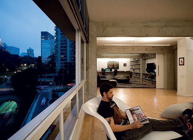 Original do prédio dos anos 1960, a grande janela de ferro restaurada banha com luz natural todo o estar, onde Mau Mau faz suas leituras. À noite, ele admira as luzes coloridas da avenida Paulista (Foto: Maíra Acayaba)