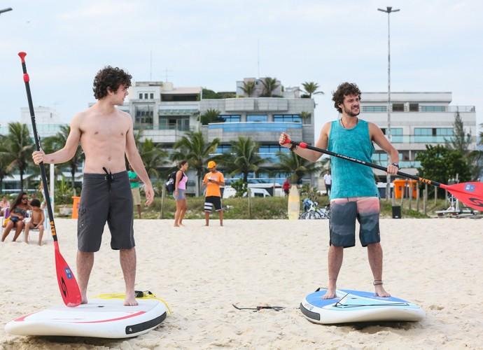 Ghilherme Lobo e Jayminho praticam stand up paddle na areia, antes de gravar no mar. Olha a concentração dos dois! (Foto: Carol Caminha/Gshow)