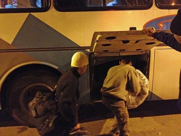 Morador de rua guarda cobertor no bagageiro do ônibus que o transportará a abrigo da Prefeitura de SP. (Foto: Helton Simões Gomes / G1)