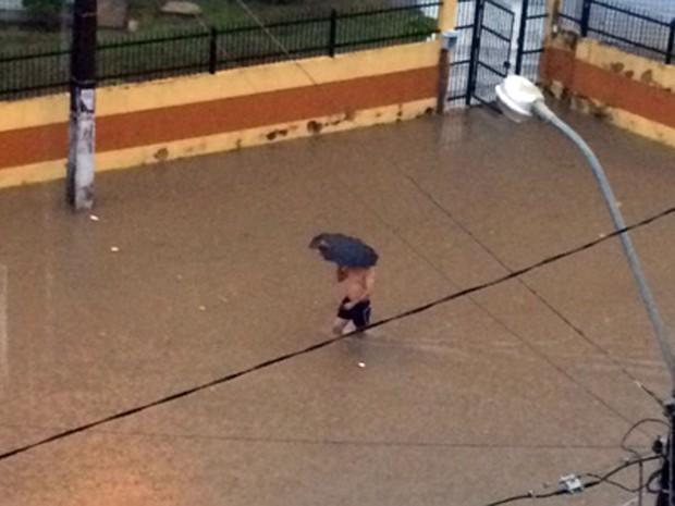 Morador de condomínio no Imbuí anda na água formada pela chuva. (Foto: Yasmin Pastor/VC no G1)