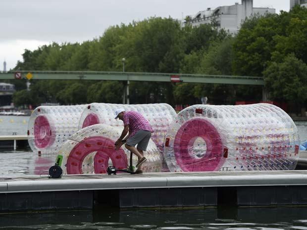 Homem prepara bóias de plásico para atividade no rio Sena, em Paris, durante inauguração de praia temporário nesta segunda-feira (20)  (Foto: AFP PHOTO / MIGUEL MEDINA)