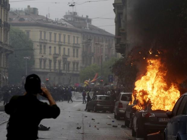 Um carro queima durante protesto contra a Exposição Universal em Milão, na Itália (Foto: Luca Bruno/AP)