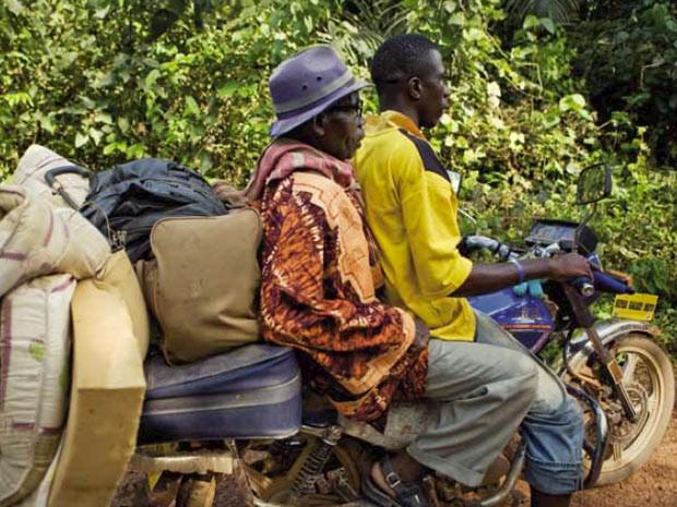 Motociclista carrega refugiado na Costa do Marfim. Mudança climática pode influenciar deslocamento de até 1 bilhão de pessoas até 2050. (Foto: Divulgação/ONU)