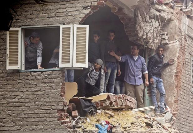 Vizinhos observam operação de resgate através de vão na parede causado pelo desabamento que deixou vários mortos no Cairo (Foto: Amr Nabil/AP)