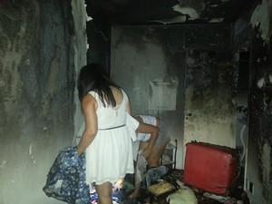 Proprietárias da casa recolhem o que restou no quartto após incêndio. (Foto: Arquivo Pessoal/Kleverton Amorim)