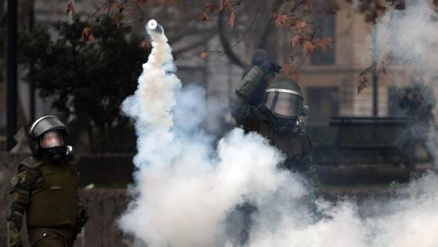 Policiais lançam bomba de gás na direção de manifestantes nesta quinta-feira (28) em frente ao Palacio de La Moneda (Foto: AFP)