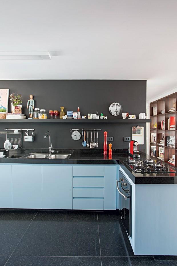 Cozinha | A mistura elegante de preto fosco da Suvinil e laminado azul Íris, da Formica, esquentam de forma original o espaço. Na prateleira, prato Fornasetti e, à esq., xícaras do Estudio Manus (Foto: Gui Morelli/Editora Globo)