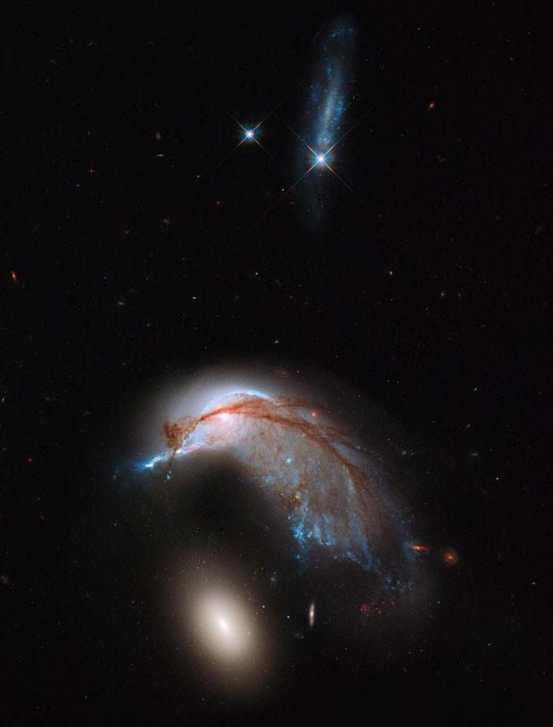 Imagem do telescópio Hubble mostra interação de galáxias conhecida como Arp 142, que lembra pinguim cuidando de ovo (Foto: AFP/NASA-ESA Hubble Heritage )