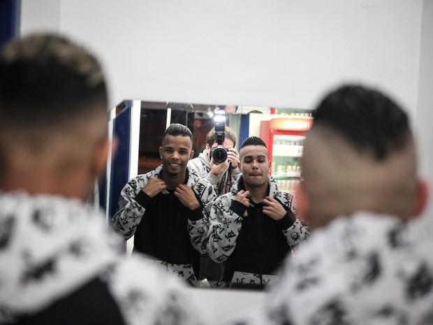 Os MCs Zaak e Jerry dão um 'tapa no visual' usando o espelho de uma loja de conveniências em parada a caminho do segundo show da noite, no Guarujá, litoral de SP (Foto: Fábio Tito/G1)