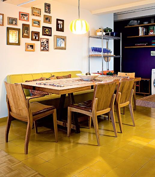 Os ladrilhos estampados da cozinha invadem a sala de jantar. No entanto, neste ambiente, eles perdem as estampas e ficam apenas com o fundo amarelo, mesma cor do sofá que substitui as cadeiras da mesa. Projeto do estúdio SuperLimão