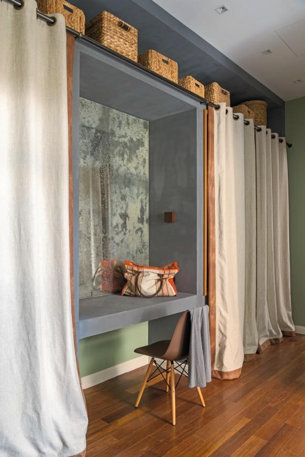 Closet. O armário de gesso acartonado pintado no tom concreto é fechado por cortinas arrematadas pelo mesmo couro que reveste o sofá da sala. Um espelho manchado, garimpado por Jean em uma obra, cria uma penteadeira, cadeira DSW e objetos da Tok & Stok (Foto: Sambacine)