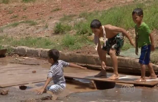 Crianças nadam em buraco aberto em rua de Goianésia Goiás (Foto: Reprodução/TV Anhanguera)