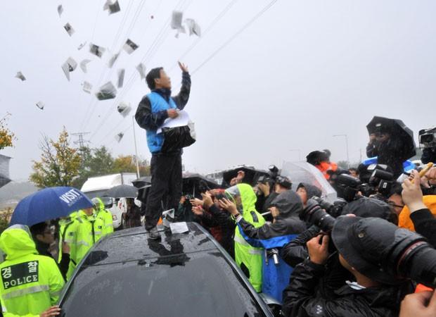 Park Sang-hak, um dos organizadores do protesto, lança folhetos após bloqueio da polícia nesta segunda (22) (Foto: Jung Yeon-Je/AFP)