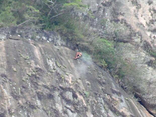 Homem aparece tentando se esconder na mata, enquanto tiro atinge o morro (Foto: Guilherme Martin Nunes)