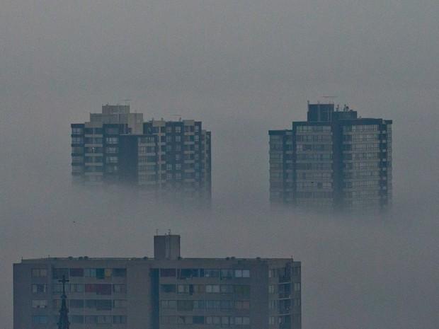 Prédios envoltos em nuvens de poluição são vistos em Santiago, no Chile. As autoridades do país relacionam o aumento da poluição com a fumaça de churrascos feitos por pessoas que comemoravam a goleada do Chile sobre o México na Copa América (Foto: Esteban Felix/AP)