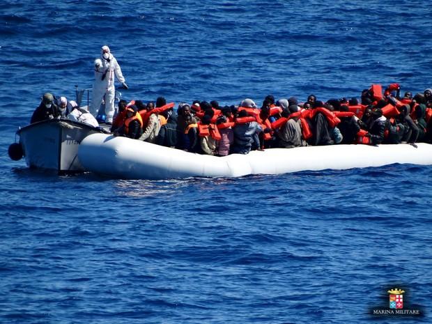 Imigrantes são vistos em um barco durante uma operação de resgate por navios da Marinha italiana na sexta-feira (18) (Foto:  Marina Militare/Divulgação via Reuters)