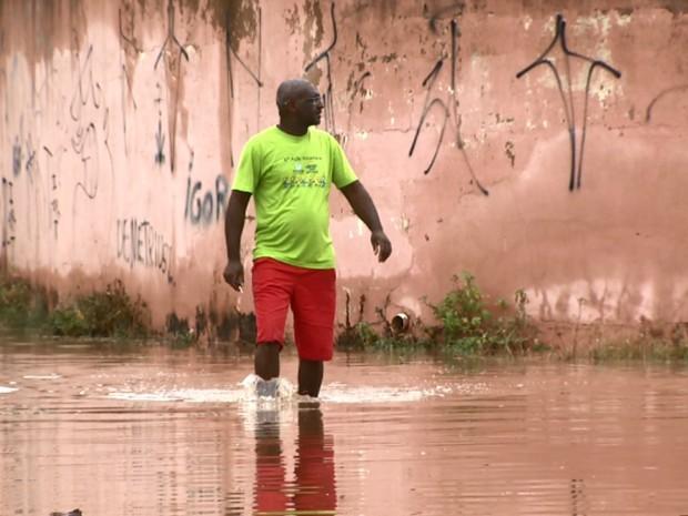 Morador anda por água de enchente após chuva em Sumaré (Foto: Reprodução/EPTV)