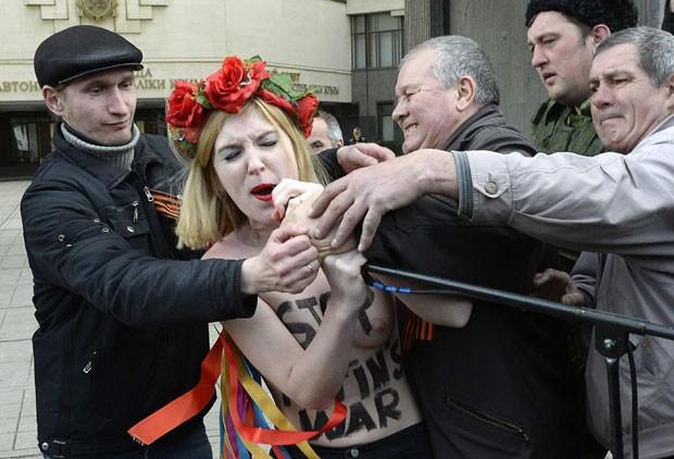 Ativista tenta pegar microfone para protestar contra Putin na Crimeia (Foto: Alexander Nemenov/AFP)
