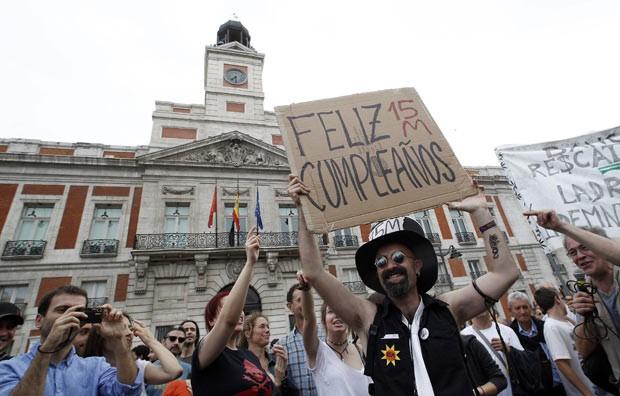 """Manifestante segura placa escrita """"Feliz Aniversário"""" em espanhol, durante protesto realizado em Madri. (Foto: Jaime Reina/AFP)"""