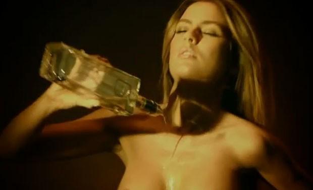 Conteúdo da garrafa passa pelos seios de modelos antes de ser vendido.  (Foto: Reprodução)