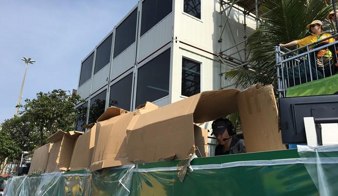Jornalistas usam caixas de papelão para se proteger do sol (Foto: Cleber Akamine)