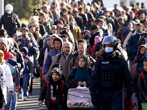 Policiais eslovenos guiam migrantes para a fronteira com a Áustria em Sentilj, na Eslovênia, nesta quarta-feira (18) (Foto: Leonhard Foeger/Reuters)