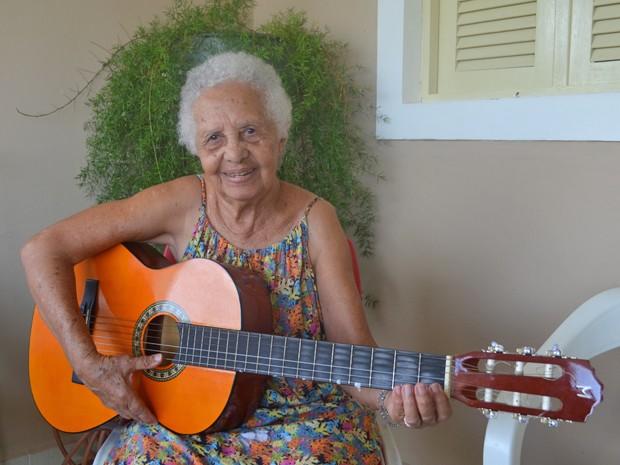 Regina está aprendendo a tocar violão em casa (Foto: Krystine Carneiro/G1)