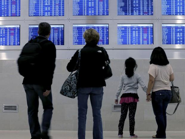 29 de outubro - Viajantes da Delta Airlines olham para uma tela com os voos desta segunda-feira em Detroit. Dezenas de voos que partem da cidade foram cancelados. (Foto: Charlie Riedel/AP)