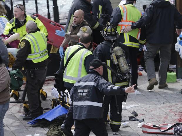 Equipes de resgate trabalham no local da explosão durante Maratona de Boston. (Foto: Charles Krupa/AP)