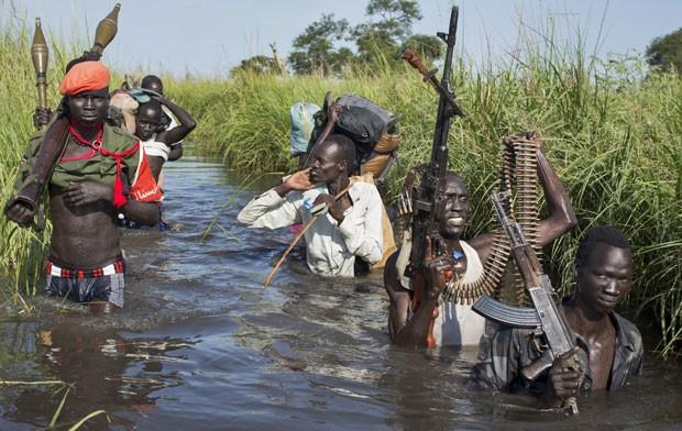 Soldados rebeldes protegem civis em caminhada por áreas alagadas no Sudão do Sul em 20 de setembro (Foto: Matthew Abbott/AP)