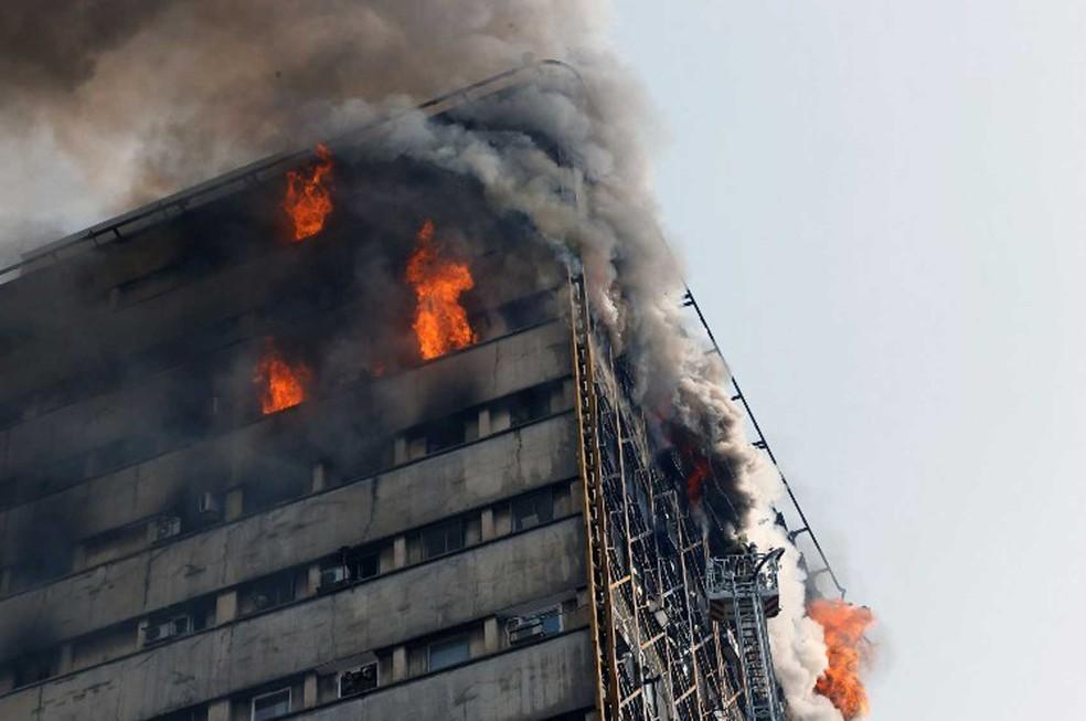 Bombeiros combatiam incêndio quando o prédio desabou  (Foto: STR / AFP)