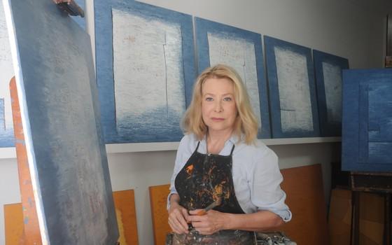 Thera Regouin posa com algumas das telas que vai expor na mostra  (Foto:  Mabel Arthou)