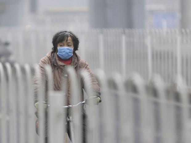Chinesa caminha nesta terça-feira (29) com máscara para proteger da poluição em Pequim, na China (Foto: China Daily/Reuters)