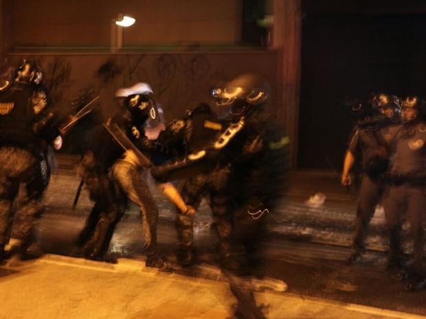 Policiais seguram manifestante após jogarem bombas de gás lacrimogêneo no Largo da Batata (Foto: Fábio Tito/G1)