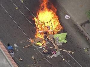 Moradores atearam fogo em lixeiras e jogavam no meio da pista (Foto: Reprodução / TV Globo)