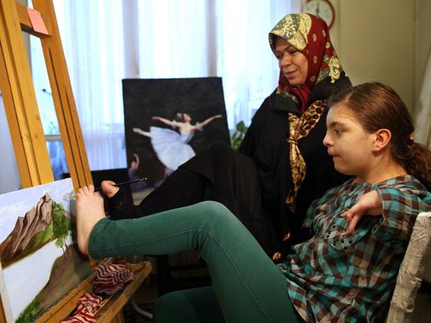 Zohreh Etezadossaltaneh ensina menina com má formação nos braços a pintar com os pés (Foto: Ebrahim Noroozi/AP)