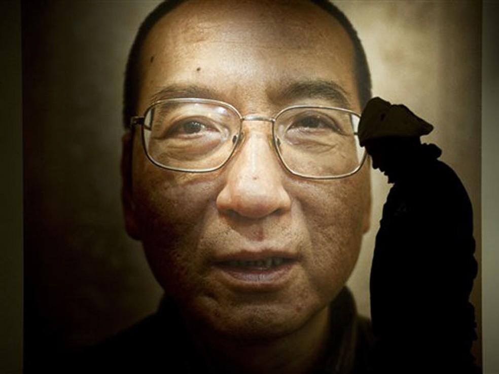 Homem passa por imagem de Liu Xiaobo em exposição no Centro Nobel da Paz, em Oslo (Foto: Odd Andersen/AFP)