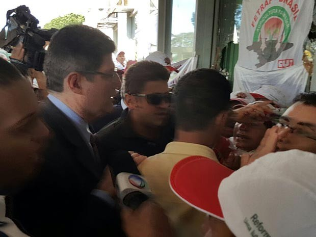 O ministro da Fazenda, Joaquim Levy, passa por manifestantes ao chegar ao ministério  (Foto: Luciana Amaral/G1)