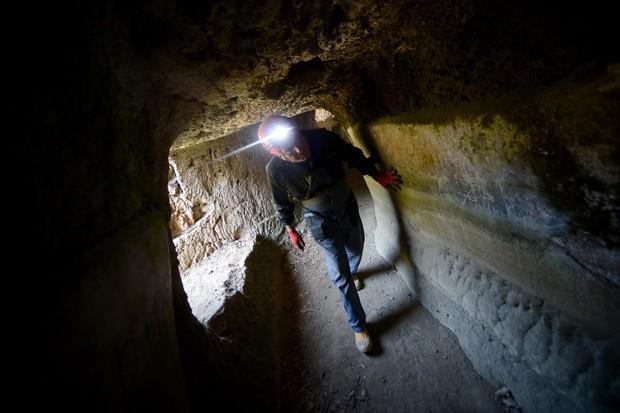 Um espeleo-arqueólogo atravessa trecho do túnel do Acqua Claudia; especialistas fizeram mapeamento dos aquedutos da Roma Antiga.  (Foto: AFP Photo/Filippo Monteforte)