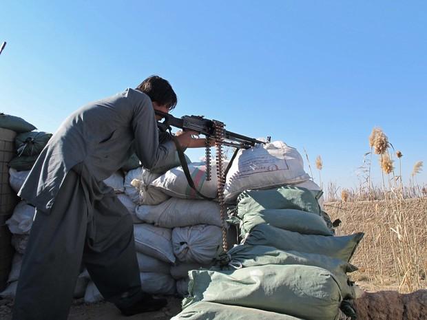 Policial afegão é visto durante batalha com talibãs no distrito de Helmand nesta quarta-feira (23) (Foto: Noor Mohammad/AFP)