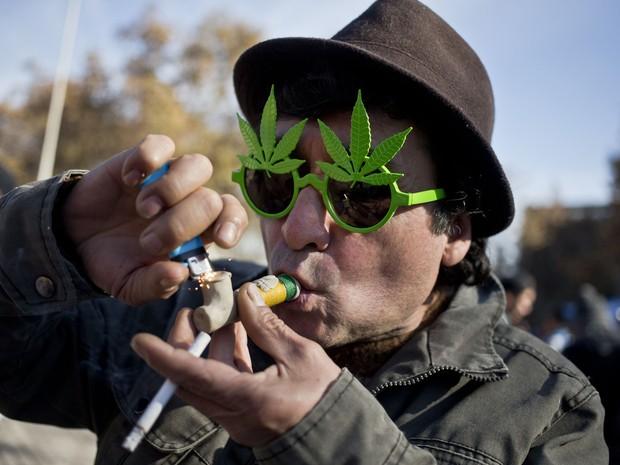 Homem fuma maconha em manifestação neste sábado (22), no Chile (Foto: AP Photo/Esteban Felix)