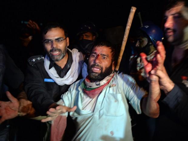 Polícia paquistanesa prende manifestante ferido neste sábado (30) em Islamabad (Foto: AFP / AAMIR QURESHI)