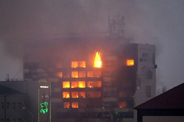 Prédio de meios de comunicação pega fogo após ataque de militantes rebeldes em Grozny, na Chechênia, na madrugada desta quinta-feira (4). Diversos policiais morreram no ataque (Foto: Elena Fitkulina/AFP)