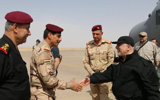 Primeiro-ministro do Iraque (à direita) aperta a mão de um oficial do exército ao chegar em Mossul e declarar vitória sobre o Estado Islâmico (Foto: HO / IRAQI PRIME MINISTER'S PRESS OFFICE / AFP)