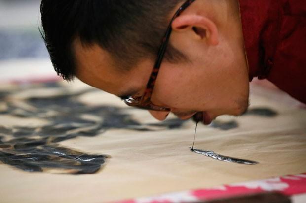 Han mergulha a língua na tinta e depois passa o órgão sobre a tela (Foto: Aly Song/Reuters)