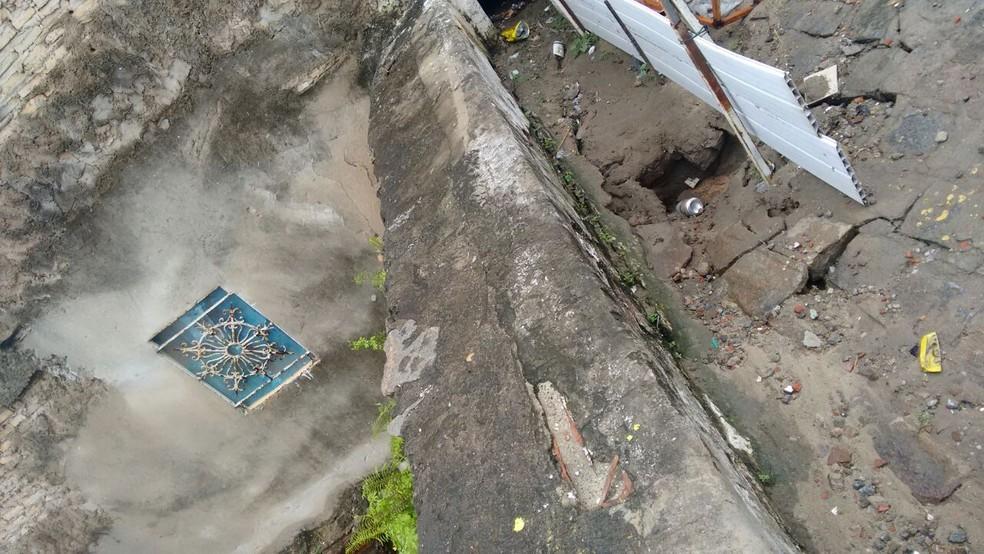 Buraco aberto pela chuva abalou estrutura de oficina, que pode desmoronar sobre casas abaixo (Foto: Divulgação/Defesa Civil )