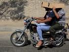 Sem capacete, motociclista usa papelão para se proteger do sol