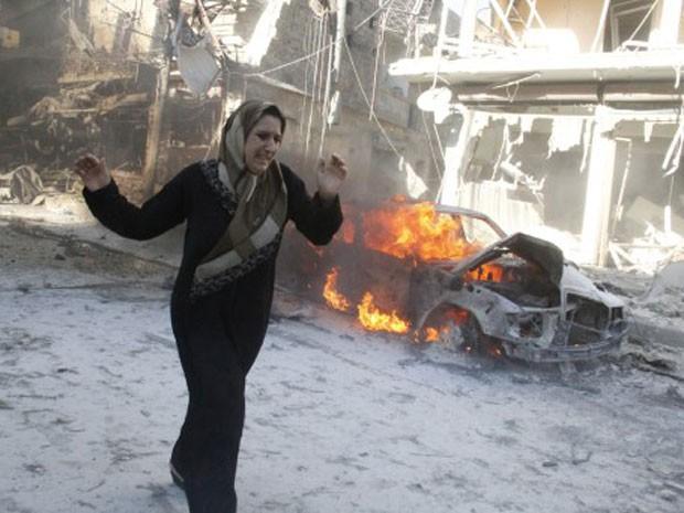 Mulher síria corre por rua de Aleppo após ataque feito por tropas pró-Assad, nesta quinta-feira (Foto: Khaled Khatib/Aleppo Media Centre/ AFP)